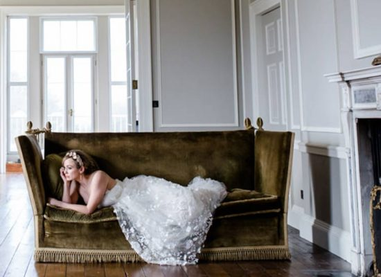 A bride reclines on the sofa at Hale Park