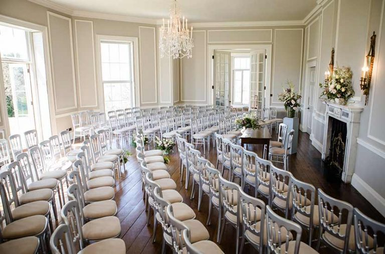 A curve of chairs look toward wedding ceremony table