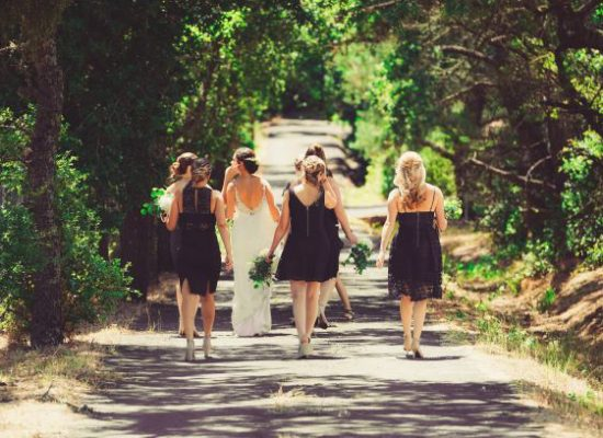 Bride and bridesmades stroll down a country lane